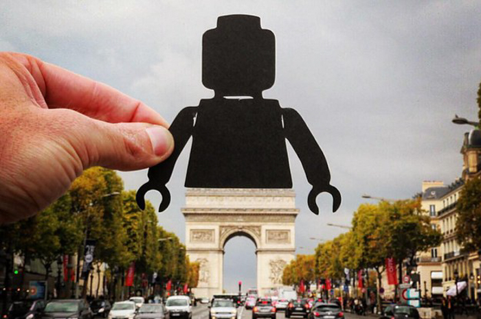 a cool forced perspective photo of a person holding the silhouette of a Lego figure over the Arc de Triomphe in Paris