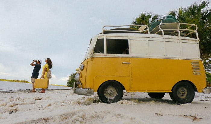 A couple on a beach with a yellow van behind them