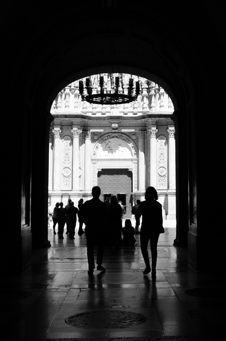 A black and white street image of people walking under an archway