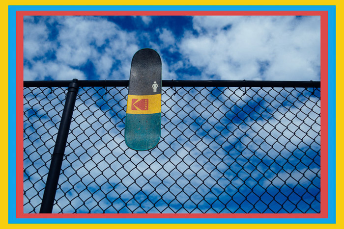 A skateboard resting on a wire fence with a colored border - Photoshop frames